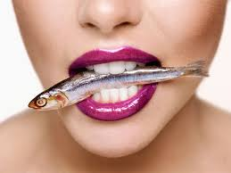 close up of woman's mouth with a sardine in it